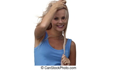 Woman grasping her hair while looking at the camera against...