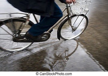 Man on bicycle in puddle of rain in flooded street splashing...