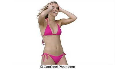 Woman in a pink bikini posing as the wind blows