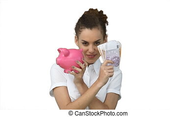 Woman with a piggy-bank and cash in her hands against a...
