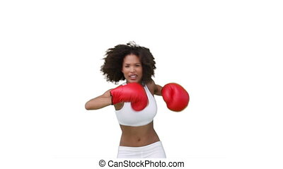 Woman boxing with her gloves on against a white background