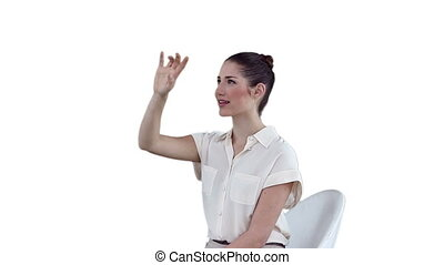 Businesswoman sitting while using a virtual touchscreen...