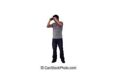 A man is looking around through binoculars