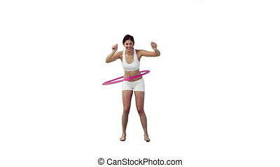 A woman is training with a hula hoop against a white...