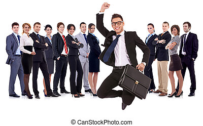 business man holding briefcase jumping in front of his team...