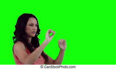 Woman interacting with a virtual touchscreen against a green...