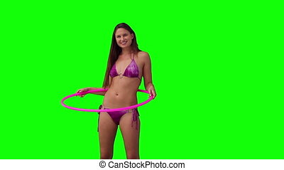 Woman playing with a hula hoop against a green background