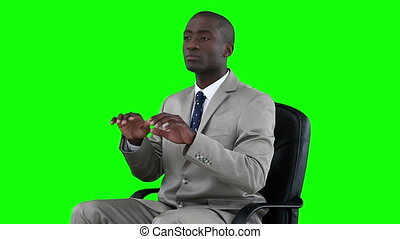 Serious businessman typing on a virtual keyboard against a...
