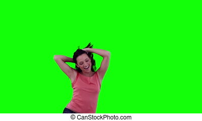 Enthusiastic woman dancing against a green background