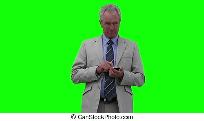 Businessman dialing on his mobile phone against a green...