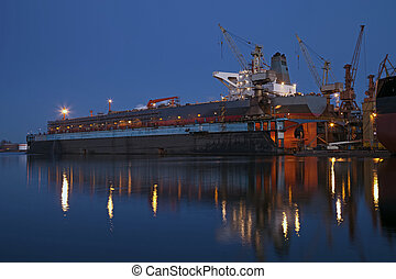 Tanker in dry dock at night - A large tanker ship is being...