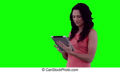 Woman happily using a tablet computer against a green...