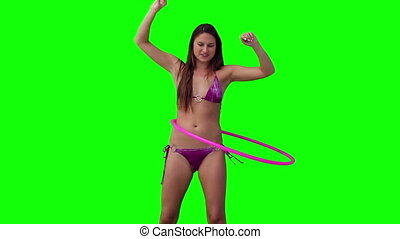 Woman spinning a hula hoop with her arms raised against a...