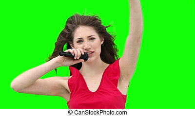 Woman waving her arms while singing into a microphone