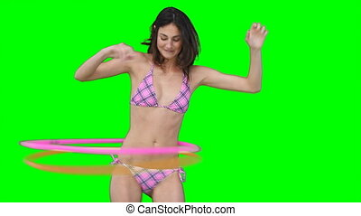 A woman playing with two hula hoops against a green...