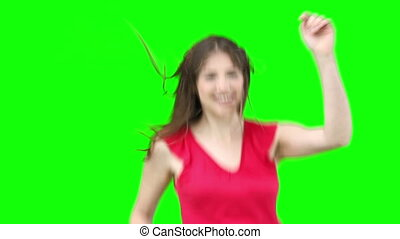 Woman jumping while waving her hair against a green...
