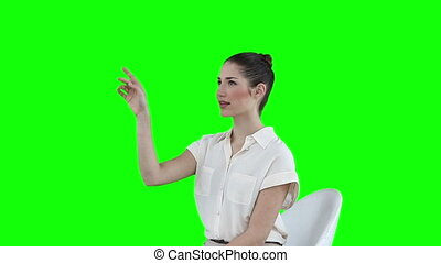 Seated businesswoman using a virtual touchscreen against a...