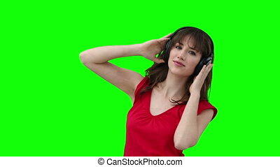 Woman dancing while holding headphones against her head