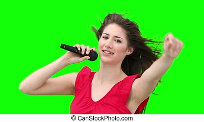 Woman gestures while singing into a microphone