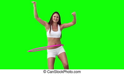 Woman happily spinning a hula hoop against a green...