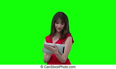 Woman scrolling through a tablet computer against a green...