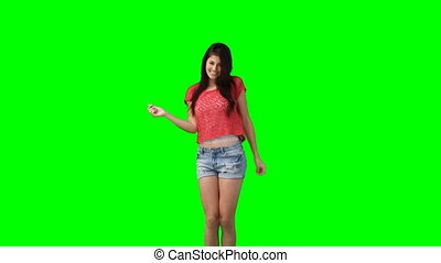 A woman jumping and dancing  against a green background