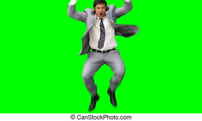 A business man jumps up and down in joy against a green...