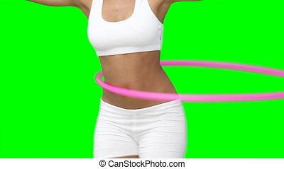 Close up of a woman using a hula hoop against a green...