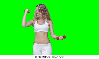 A woman training against a green background