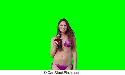 A woman in a bikini holding a drink against a green...