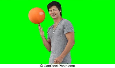 A man spinning a basketball on his hand against a green...