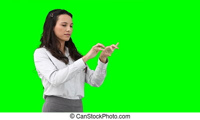 A business woman using a virtual keyboard against a green...