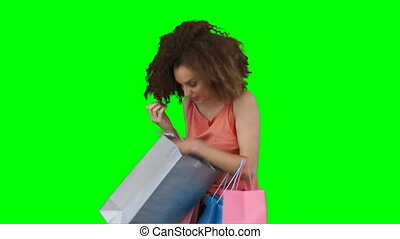A woman with shopping trying on her scarf against a green...