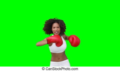 A woman practising her boxing against a green background