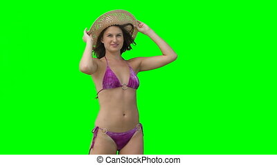 A woman in her bikini trying to hold on to her hat as the wind blows