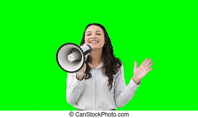 A woman talks on a megaphone against the green background
