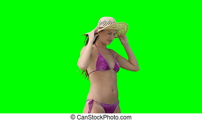 A woman in a bikini eith her hat falling off