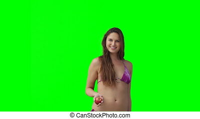 A woman in a bikini throwing an apple up and down
