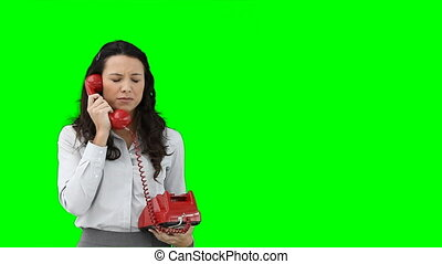 A business woman using a red telephone