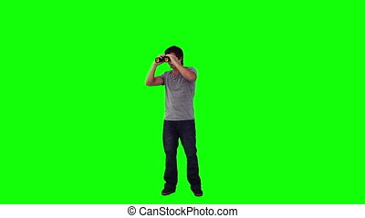 A man is looking through binoculars against a green...