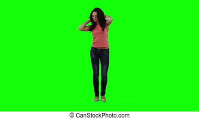 A woman is dancing on her own in front of a green background