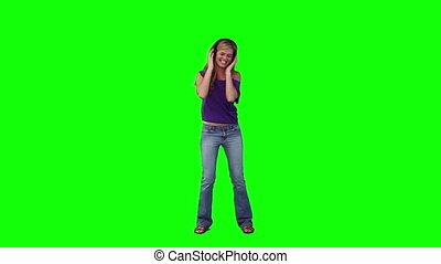 A woman with headphones on is dancing