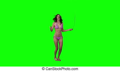 A woman in a bikini is using a skipping rope against a green...
