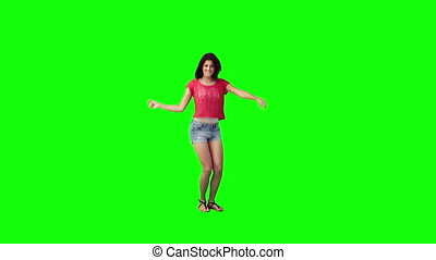 A young woman is dancing on her own against a green...