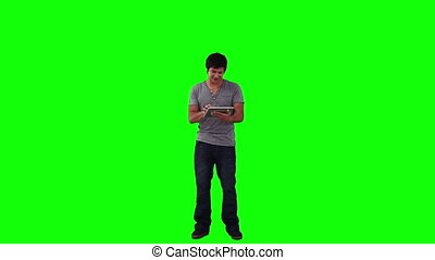 A man is using a tablet computer against a green background