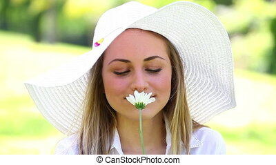 Smiling blonde woman holding a flower