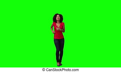 A happy woman is dancing against a green background