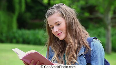 Smiling young woman reading a book in a park