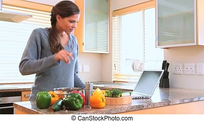 Woman cooking while looking at the recipe in her kitchen