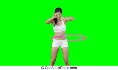 A woman training with a hula hoop in front of a green...